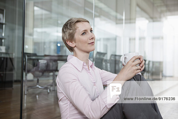 Germany  Munich  Businesswoman in office  sitting on floor with coffee cup