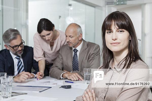 Deutschland  München  Geschäftsleute im Konferenzraum  Frau im Vordergrund mit Blick auf die Kamera