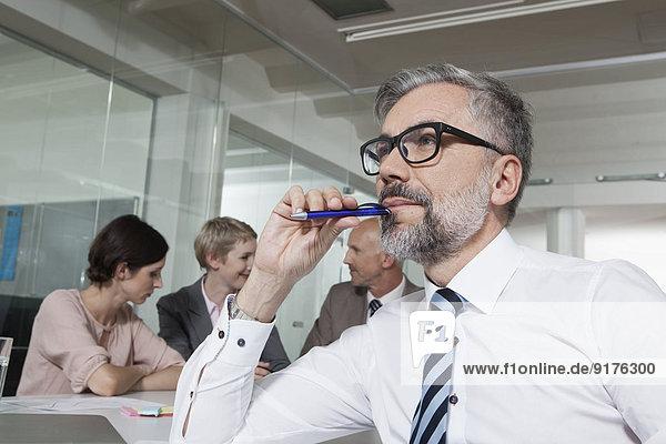 Deutschland  München  Geschäftsleute im Konferenzraum  Mann mit Stift und Mund