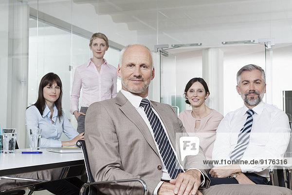 Deutschland  München  Geschäftsleute im Konferenzraum  Mann im Vordergrund mit Blick auf die Kamera