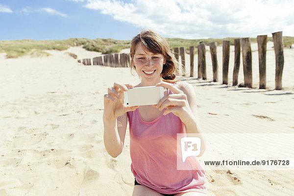 Porträt einer Frau  die mit ihrem Smartphone am Strand fotografiert.