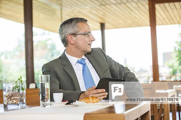 Geschäftsmann im Restaurant mit digitalem Tablett