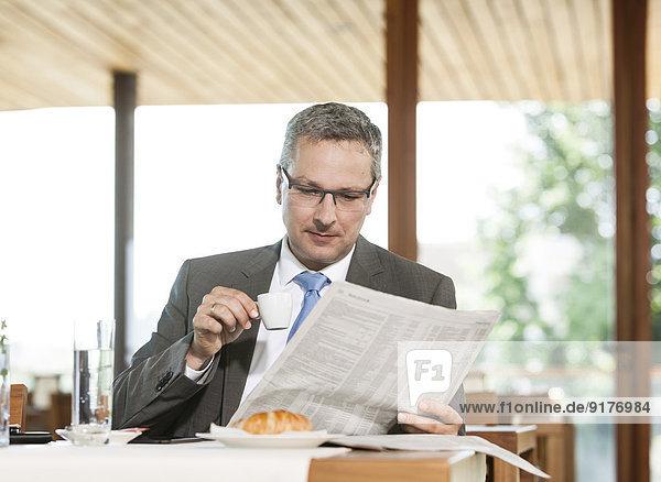 Geschäftsmann beim Zeitungslesen im Restaurant