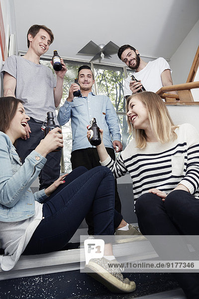 Group of creative professionals drinking beer in staircase