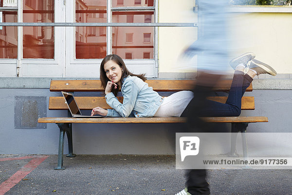 Frau mit Laptop auf der Bank liegend mit vorbeikommender Person