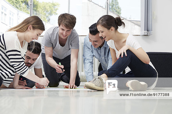 Gruppe von Kreativen  die auf dem Boden arbeiten