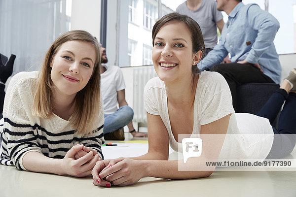 Zwei lächelnde junge Frauen liegen auf dem Boden.