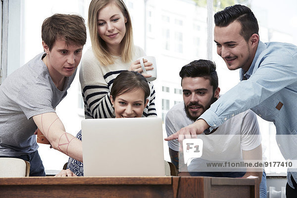 Gruppe von Kreativprofis mit Laptop am Tisch