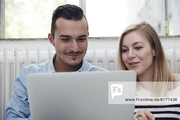 Smiling man and woman using laptop