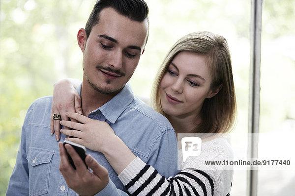 Paar mit Handy am Fenster