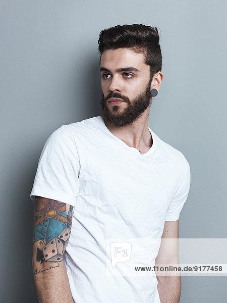 Portrait des tätowierten brünetten Mannes vor grauem Hintergrund