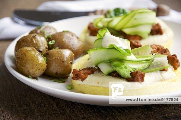 Polenta mit veganer Käsesauce  würzigen Tofu-Stücken und Spargel  serviert mit Salzkartoffeln