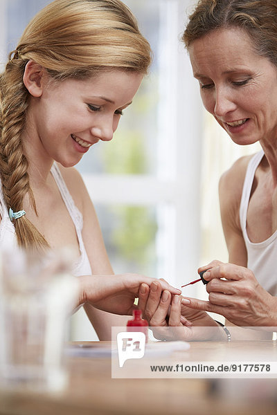 Mother varnishing the nails of her daughter at home