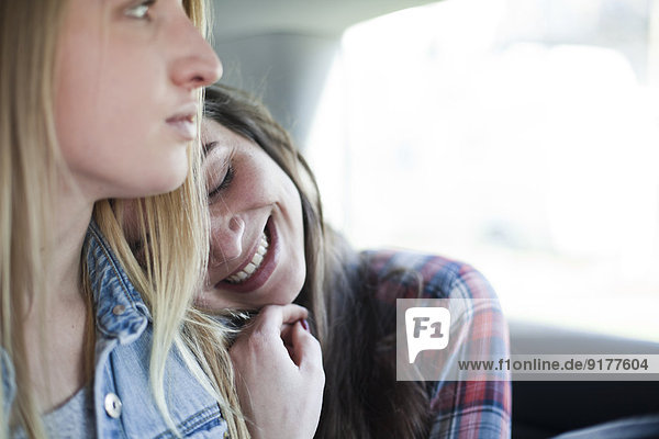 Two young women sitting on back seat of a car