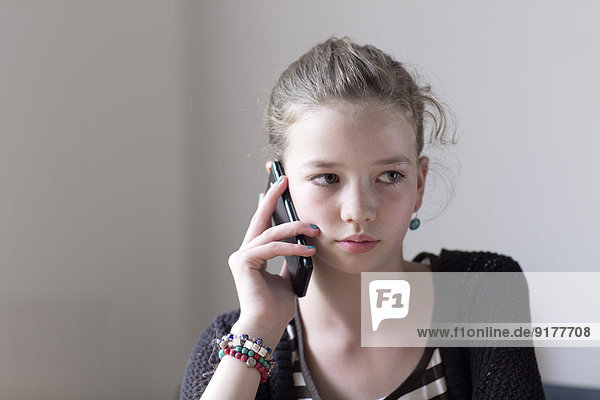 Portrait of girl telephoning with smartphone at home