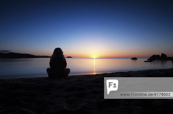 Spanien  Menorca  Frau beim Sonnenuntergang am Playa de Cavalleria