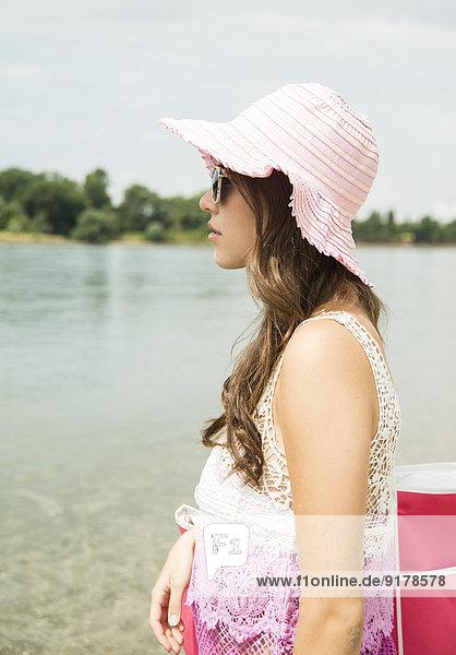 Junge Frau mit Sommerhut am Strand