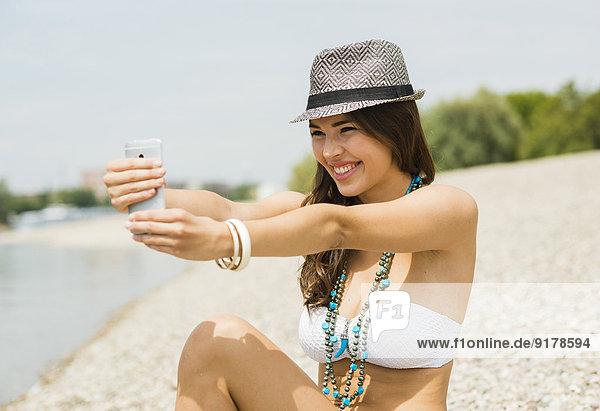 Porträt einer lächelnden jungen Frau  die einen Selfie mit ihrem Smartphone am Strand nimmt.