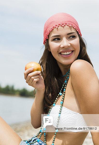 Porträt einer lächelnden jungen Frau mit Apfel am Strand