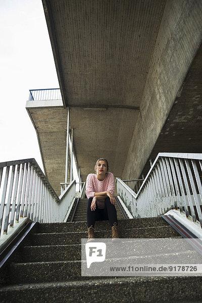 Junge Frau auf der Treppe sitzend wartet