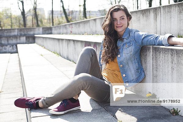 Entspannte junge Frau im Freien sitzend