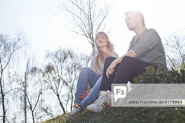 Entspanntes junges Paar auf der Wiese sitzend