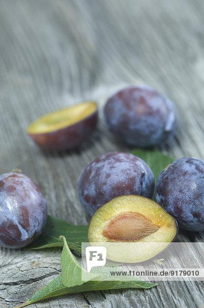 Geschnittene und ganze Pflaumen  Prunus domestica subsp. domestica  und Blätter auf grauem Holz