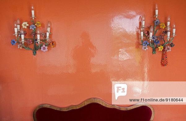 Zwei alte Wandlampen hängen an der glänzend roten Wand