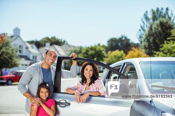 Porträt der Familie am Auto in der Einfahrt