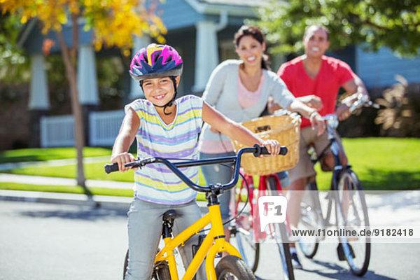 Porträt der lächelnden Familie beim Radfahren auf der Straße