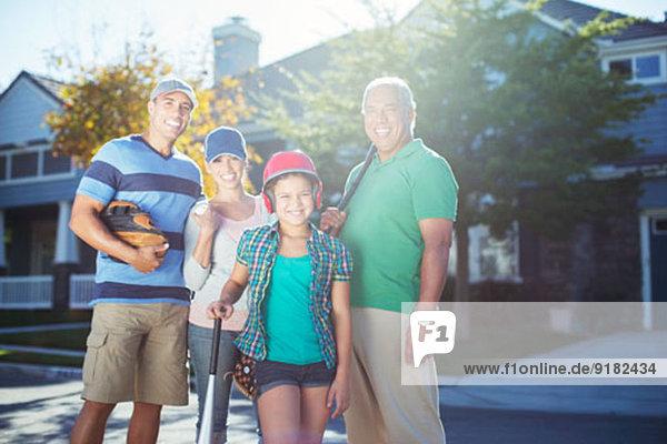 Porträt der lächelnden Mehrgenerationen-Familie mit Baseballschläger in der Straße