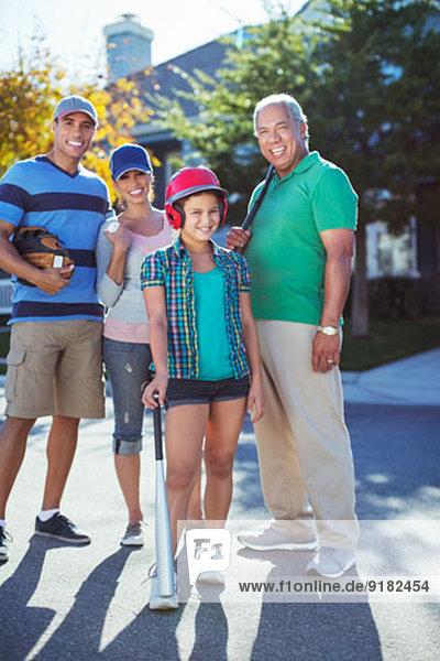 Porträt der glücklichen Mehrgenerationen-Familie beim Baseball auf der Straße