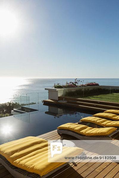 Sonnenschein über den Liegestühlen am Pool mit Blick auf den Ozean
