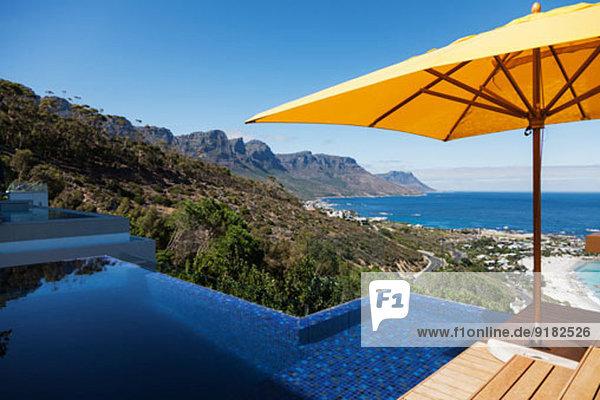Blick auf den Ozean von der sonnigen Terrasse mit Infinity-Pool