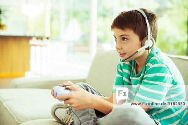 Junge spielt Videospiele auf dem Sofa