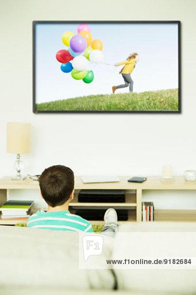 Junge beim Fernsehen im Wohnzimmer