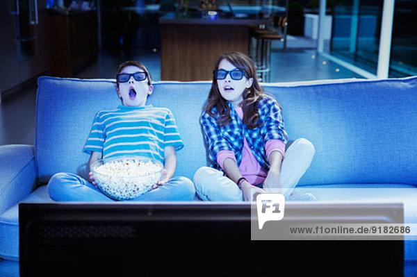Kinder beim 3D-Fernsehen im Wohnzimmer