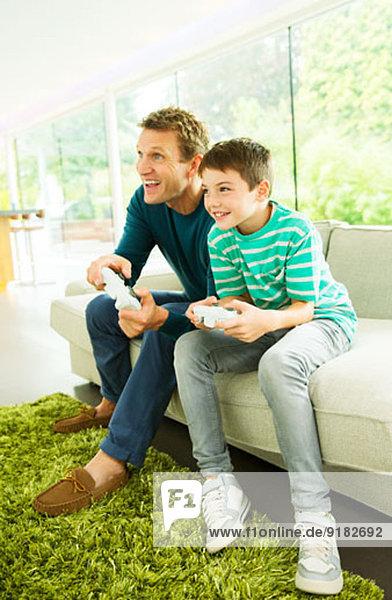 Vater und Sohn spielen Videospiele im Wohnzimmer