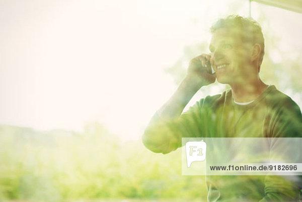 Mann spricht am Handy am Fenster