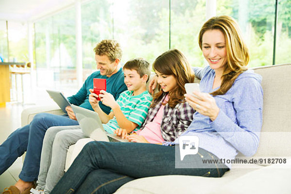 Familie mit Technik auf dem Sofa