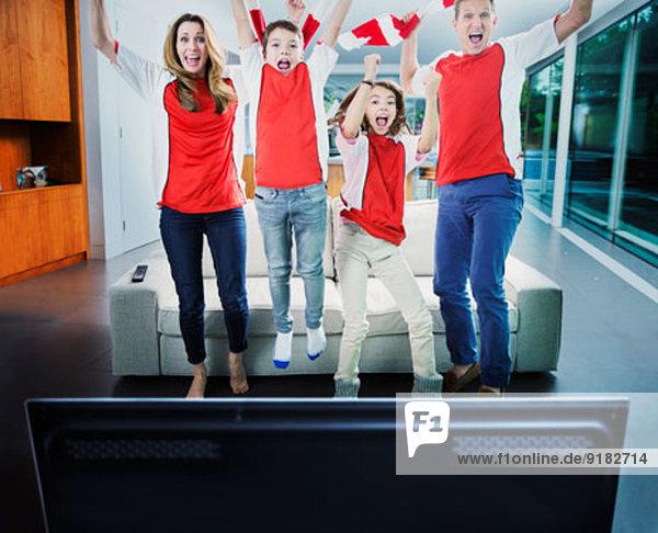 Familienjubel vor dem Fernseher im Wohnzimmer