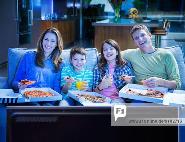 Familie isst Pizza vor dem Fernseher im Wohnzimmer