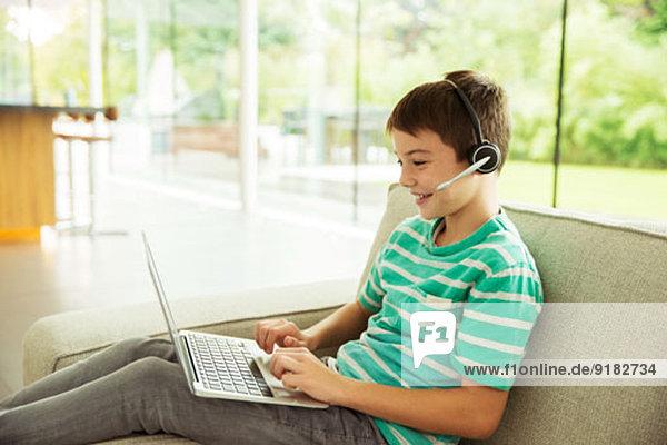 Junge mit Headset und Laptop auf dem Sofa
