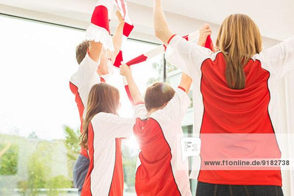 Familie in Sporttrikots jubelt zusammen