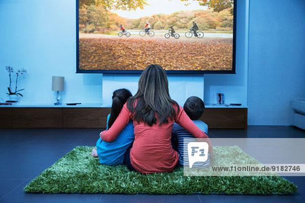 Mutter und Kinder beim Fernsehen im Wohnzimmer