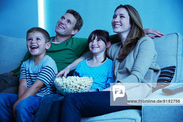 Familie beim Fernsehen im Wohnzimmer