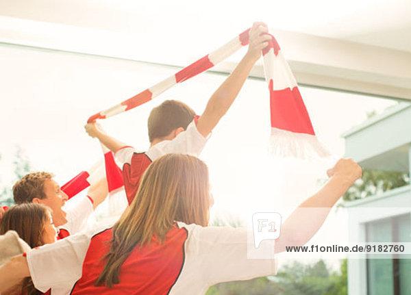 Familie im Sporttrikot jubelnd im Wohnzimmer