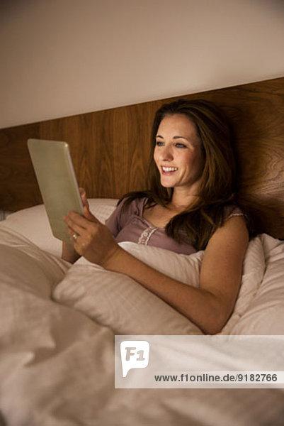 Frau mit digitalem Tablett im Bett