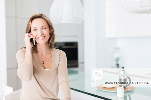 Woman talking on cell phone at breakfast table