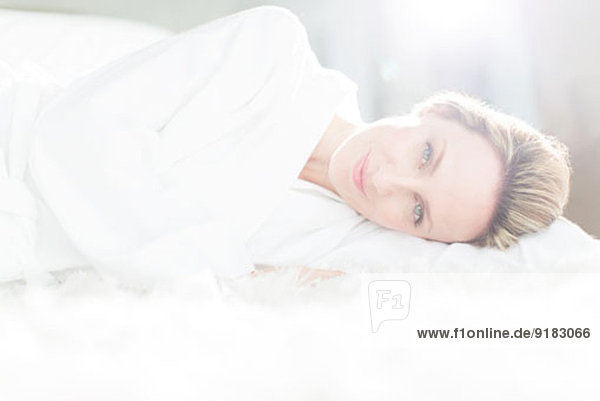 Frau im Bademantel auf dem Bett liegend